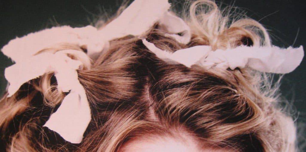 Haar van dochter krullen met katoenen papillotten