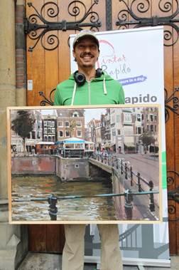 De trotse winnaar Daniel Parra Lozano met zijn schilderij gemaakt bij de Haarlemmerstraat en de Singel.